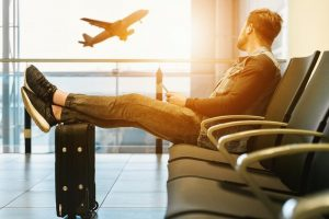 Man sitting on gang chair with feet on luggage looking at airplane: How to find internships abroad