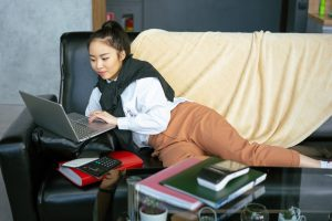 A girl lying on a couch looking at her computer -Interning Remotely - 7 Most Unexpected Challenges