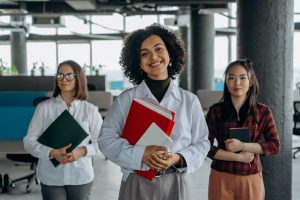 Three ladies holding files - Why MBAs are Still a Mark of Distinction in 2021